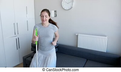 Happy woman is washing floor using mop, singing a song and dancing in her modern flat.