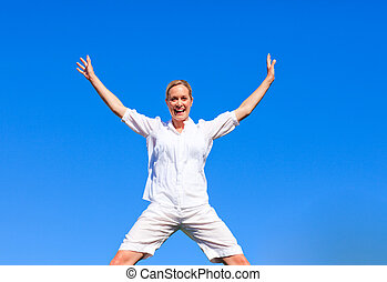 Happy woman jumping against blue sky