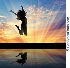 happy woman jumping at sunset