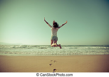 Happy woman jumping at the beach. Summer vacation concept. Freedom