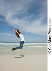 Happy woman jumping for joy at beach