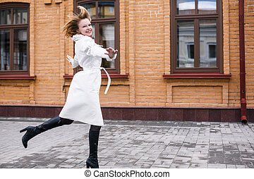 Happy woman jumping in the street