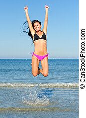 Happy woman jumping in the water at the beach