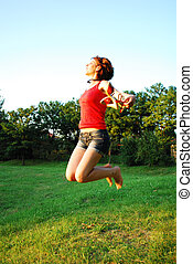 Happy woman jumping on grass