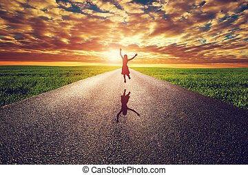 Happy woman jumping on long straight road, way towards...