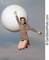 happy woman jumping with big, white balloon