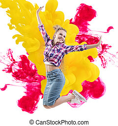 Happy woman jumps over paints explosion background.