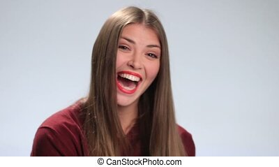 Happy woman laughing against white background - Attractive...
