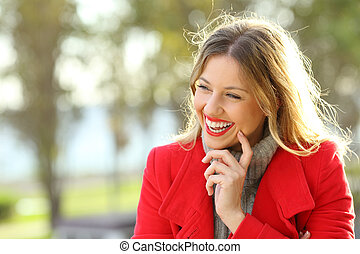 Portrait of a happy woman laughing warmly clothed with a red jacket in a park in winter