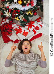 Happy woman laying near Christmas tree and pointing on copy space