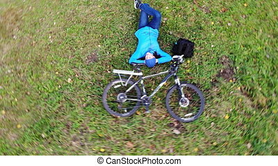 Happy woman laying on green grass with her bicycle, rider on...
