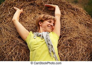 Happy woman lies on a haystack