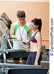 Happy woman listening to her coach after doing exercises on...