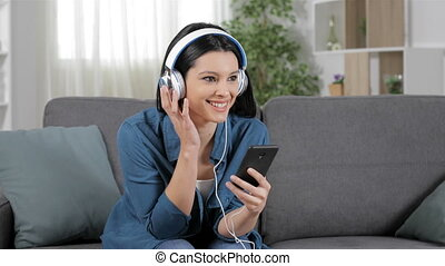 Happy woman listening to music from cell phone sitting on a...