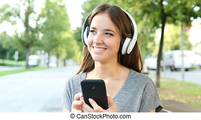 Happy woman listening to music on phone - Happy woman...