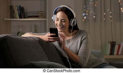 Happy woman listening to music on phone in the night - Happy...