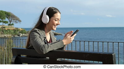 Happy woman listening to music sitting on a bench
