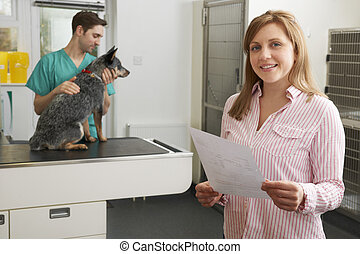 Happy Woman Looking At Bill In Veterinary Surgery