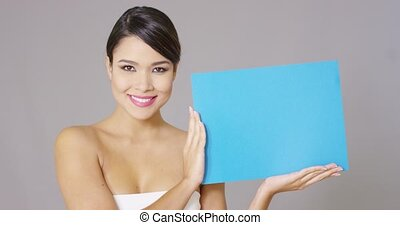 Happy woman looking at blue card in her hands
