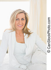Happy woman looking at camera posing on her bed