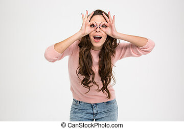 Happy woman looking at camera through fingers