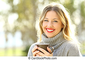 Happy woman looking at camera with a cup of coffee