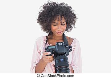 Happy woman looking at digital camera