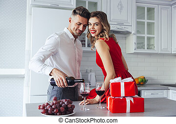 Happy woman looking camera while her man pouring wine into glasses at home