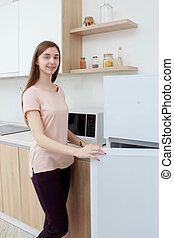 Happy woman looking for something in the fridge at home