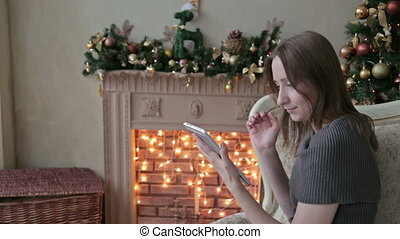 Happy woman looking in tablet PC in front of Christmas tree