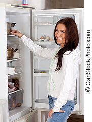 Happy woman looking in the fridge at home