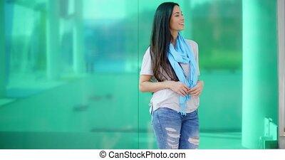Happy woman looking sideways in front of glass