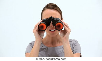 Happy woman looking through binoculars against a white background