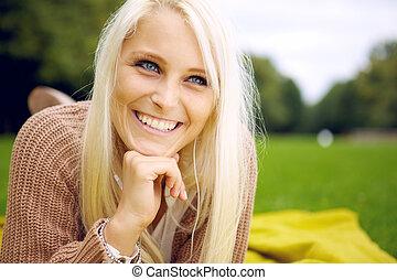 Happy woman lying in a park