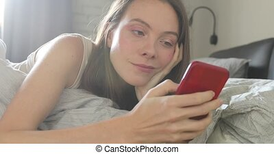 Happy woman lying on bed smiling text smartphone