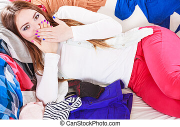Happy woman lying on clothes covering mouth.