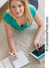 Happy woman lying on floor doing her homework using tablet...