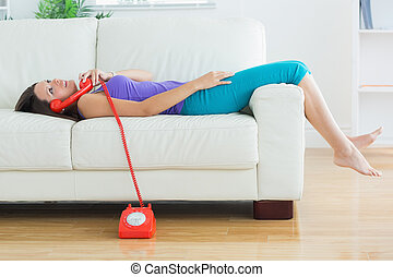 Happy woman lying on the sofa and phoning in the living room