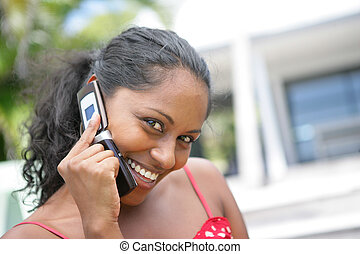 Happy woman making a phone call outdoors