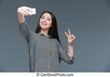 Happy woman making selfie photo