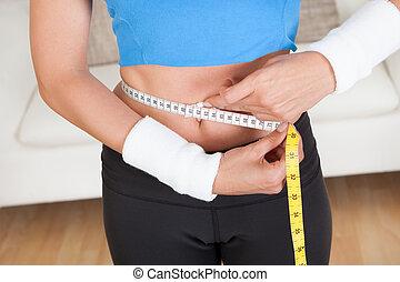Happy woman measuring her waist