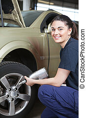 Happy Woman Mechanic Tire Change - Portrait of a happy...