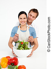 Happy woman mixing a salad with her boyfriend in the kitchen