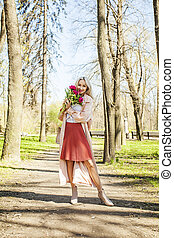 Happy woman model with flowers outdoors. Blonde female model with peony