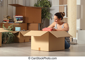 Happy woman moving home unboxing belongings in the night