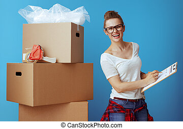 happy woman near cardboard box marking moving checklist on blue