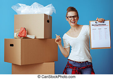 happy woman near cardboard box showing moving checklist on blue