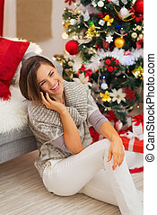 Happy woman near Christmas tree having phone call