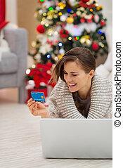 Happy woman near Christmas tree shopping online