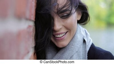 Happy woman near wall